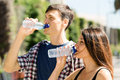 Couple drinking water from plastic bottles Royalty Free Stock Photo