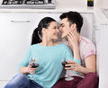 Couple drinking wine in their kitchen young kissing Stock Photos