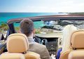 Couple driving in cabriolet car over sea shore Royalty Free Stock Photo
