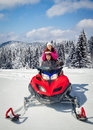 Couple driving snowmobile in winter mountain Stock Photography