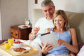 Couple eating breakfast in bed with digital tablet looking at screen smiling Stock Image