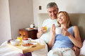 Couple eating breakfast in bed together lying next to each other smiling Royalty Free Stock Image