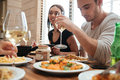 Couple eating and drinking wine with friends on the kitchen Royalty Free Stock Photo