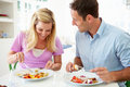 Couple eating meal at home together in kitchen sitting table smiling Stock Photo