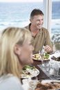 Couple eating meal near the sea happy middle aged men enjoying food with women in foreground seaside Royalty Free Stock Photography