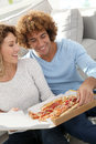 Couple eating pizza cheerful at home having for supper Stock Image