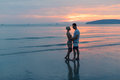 Couple Embracing On Beach At Sunset, Young Tourist Man And Woman Hug On Seaside Royalty Free Stock Photo