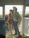Couple embracing on beach view through campervan door full length of young Stock Photography