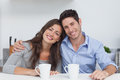 Couple embracing each other in the kitchen with a cup of coffee Stock Photo