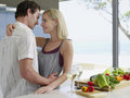 Couple embracing with fresh vegetables on kitchen counter loving young Royalty Free Stock Photo