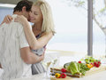 Couple embracing with fresh vegetables on kitchen counter romantic young Royalty Free Stock Photos