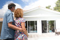Couple embracing in front of new modern house, back view Royalty Free Stock Photo