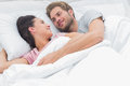 Couple embracing and looking at each other while they are lying in bed Royalty Free Stock Photography