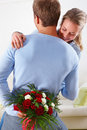 Couple embracing man hiding flowers Stock Photo