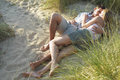 Couple embracing in secluded spot at beach young lying and Stock Photos