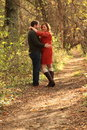 Couple embracing on trail in fall wooded area as woman coyly smiles at camera Royalty Free Stock Photo