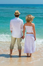 Couple enjoying at beach back view on and looking on the blue sea Royalty Free Stock Photography