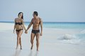 Couple enjoying on the beach walking holding hadas Stock Photography