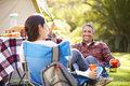 Couple enjoying camping holiday in countryside smiling Stock Photos