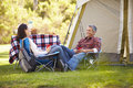 Couple enjoying camping holiday in countryside smiling Stock Images