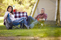 Couple enjoying camping holiday in countryside smiling to camera Stock Photos