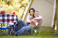 Couple enjoying camping holiday in countryside smiling to camera Royalty Free Stock Images