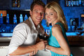 Couple enjoying drink in bar smiling to camera Royalty Free Stock Photo