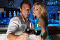 Couple enjoying drink in bar smiling to camera Royalty Free Stock Photos