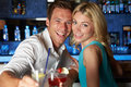 Couple enjoying drink in bar smiling to camera Stock Image