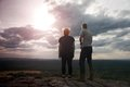 Couple enjoying fantastic moments during sunset . Young pair of hikers on the peak of rock empires park and watch over valley. Royalty Free Stock Photo