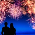 Couple enjoying a fireworks display spectacular on deep blue sky with silhouettes of young watching it Royalty Free Stock Photography