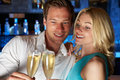 Couple enjoying glass of champagne in bar smiling to camera Royalty Free Stock Images