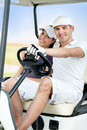 Couple enjoying golf course close up of cheerful young riding in cart Stock Photo
