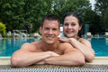 Couple enjoying holidays at pool edge summer public swimming Royalty Free Stock Photos