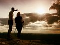 Couple enjoying marvellous moments during sunset . Young pair of hikers on the peak of rock watch  to Sun. Royalty Free Stock Photo