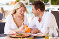 Couple enjoying meal in outdoor restaurant smiling Royalty Free Stock Photo