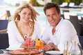 Couple enjoying meal in outdoor restaurant smiling Stock Photo