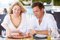 Couple enjoying meal in outdoor restaurant smiling Stock Photos
