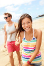 Couple enjoying romantic beach vacation holiday young modern trendy cool multi ethnic having fun laughing together smiling Stock Photos