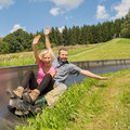Couple enjoying summer sledge portrait of young ride Royalty Free Stock Photos