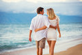 Couple enjoying sunset on the beach romantic beautiful tropical Royalty Free Stock Photo