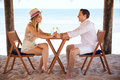Couple enjoying their vacation at the beach profile view of an attractive young holding hands accross a table and having a good Royalty Free Stock Images