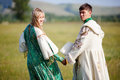 Couple in ethnic costumes hold hands turned back to  camera. Royalty Free Stock Photo