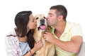 Couple with eyes closed kissing dog over white background Stock Photo