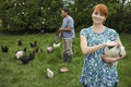 Couple feeding hens on grassland young smiling Royalty Free Stock Images