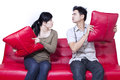 Couple fighting on red sofa isolated with white background Stock Photo