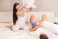 Couple fighting together with pillows in bed portrait of happy loving having pillow fight Stock Image