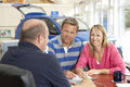 Couple filling in paperwork in car showroom Stock Photo