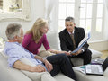 Couple with financial advisor at sofa mature sitting on Royalty Free Stock Images