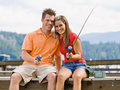 Couple fishing on pier Stock Photo